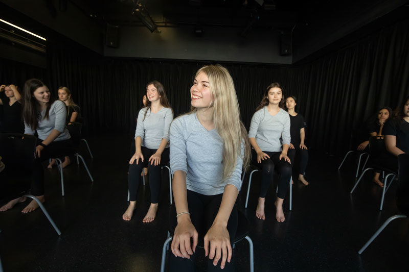 Girls sitting in chairs in Dance studio