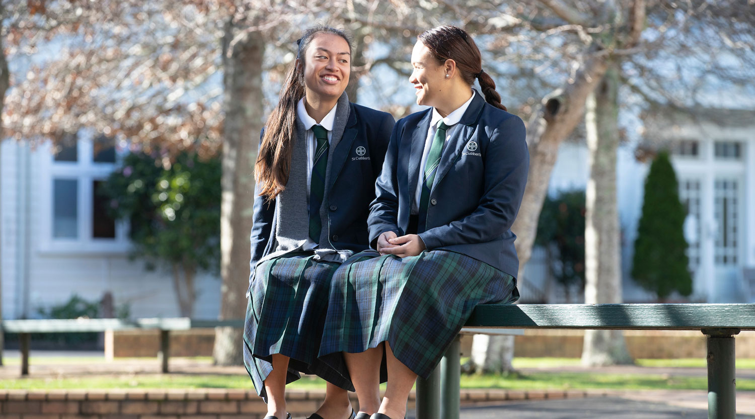Two senior girls sitting on bench wearing St Cuthbert's uniform
